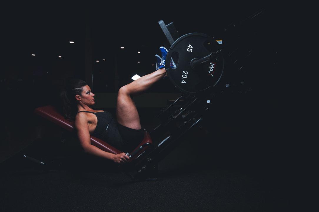 women using leg press machine with weights